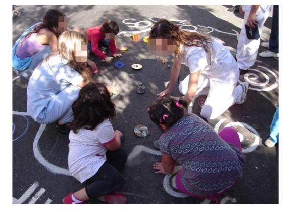 Figura 2: Profesionales jugando con niñas/os del barrio en el CUJUCA en la Puerta del Centro de Salud